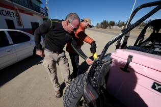 Bill and Tiberio add oil to the Arctic Cat in hopes of getting it started.