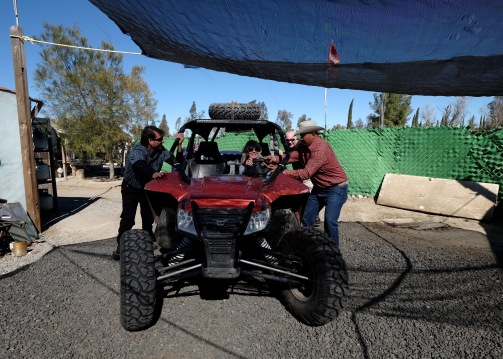 Suzanna steers while Tiberio, Bill and some local men push the Arctic Cat back to the trailer